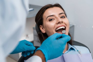 selective focus of dentist in latex gloves holding dental mirror near woman