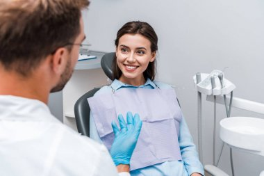 selective focus of attractive woman looking at dentist in clinic