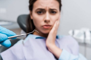 selective focus of dentist in latex glove holding dental instrument near woman having toothache