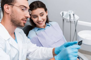 selective focus of handsome dentist in glasses holding x-ray near attractive woman