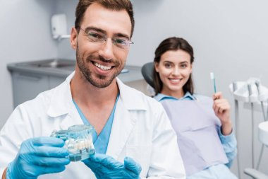 selective focus of happy dentist in glasses holding teeth model near cheerful patient with toothbrush