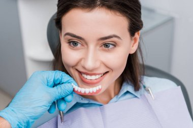 cropped view of dentist holding prosthesis near happy girl in dental clinic