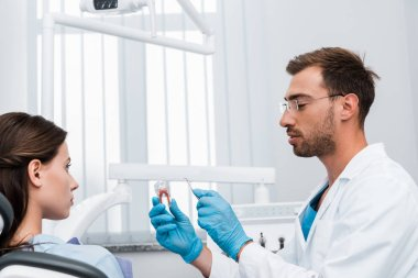 selective focus of dentist in glasses holding dental instrument and tooth model near girl