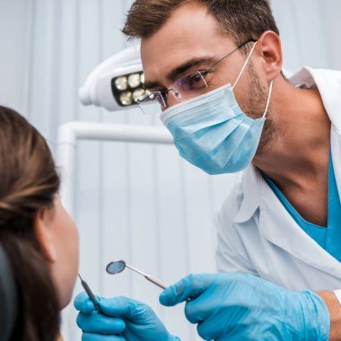 selective focus of dentist in glasses and medical mask holding dental instruments near patient