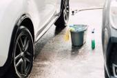 selektivní zaměření bílého auta blízko černé auto a kbelíku s houbou