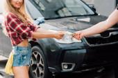 vágott kilátás az ember, amely pénzt a boldog nő autómosó