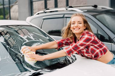 Positive girl washing windshield of car with sponge and foam stock vector