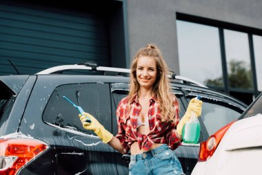 selective focus of happy girl holding spray bottle and squeegee near automobiles