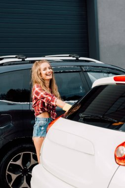 happy woman standing and smiling near modern automobiles
