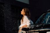 přitažlivá a mokrá dívka stojící blízko černého luxusního vozu