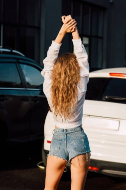 back view of young woman in shorts standing near modern cars
