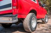 piros autó piszkos kerekek a földön az erdőben, napsütéses napon