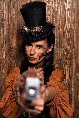 selective focus of serious steampunk woman in top hat with goggles aiming with pistol at camera on wooden