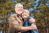 usmívající se starší dvojice turistů, kteří za slunečného dne objímali zavřené oči
