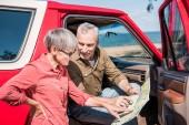 Fényképek mosolygó vezető utazó ül a piros autót, és nézi a térképet a feleségével