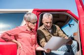 mosolygó vezető utazó ül a piros autót, és nézi a térképet a feleségével