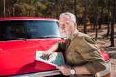Fényképek töprengő vezető idegenforgalmi álló közelében piros autó és a gazdaság Térkép napsütéses nap