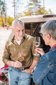 happy senior couple standing near car with wine glasses and looking at each other