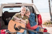 happy senior couple with acoustic guitar near car in sunny day