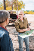 selective focus of senior couple with map near car in forest in sunny day