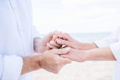 Fotografie cropped view of senior couple in white shirts holding hands under blue sky