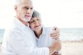 šťastný starší pár v bílých kočkách objímající pláž