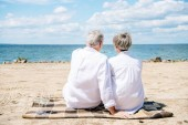 back view of senior couple in white shirts sitting on blanket at beach