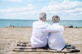 Fotografie back view of senior couple in white shirts sitting on blanket and embracing at beach