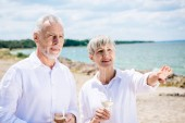 smiling senior couple holding wine glasses with wine and looking away at beach