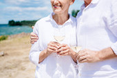 Fotografie cropped view of smiling senior couple embracing and holding wine glasses with wine at beach