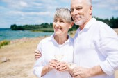 smiling senior couple embracing and holding wine glasses with wine at beach