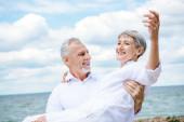 smiling senior man in white shirt holding wife under blue sky near river