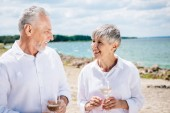 smiling senior couple holding wine glasses with wine and looking at each other at beach