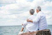 back view of senior couple in white shirts sitting on stone and embracing near river