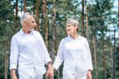 šťastný starší pár v bílých košili, který se drží za ruce a dívá se na sebe v lese