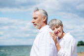 happy senior couple in white shirts standing under blue sky in sunny day