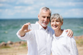 Fotografie smiling senior couple in white shirts embracing and taking selfie at beach