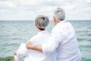 back view of senior couple in white shirts embracing near river under blue sky