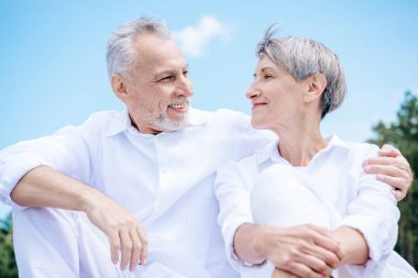 Happy smiling senior couple in white shirts embracing and looking at each other under blue sky stock vector