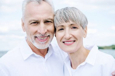 Front view of smiling happy senior couple in white shirts looking at camera stock vector