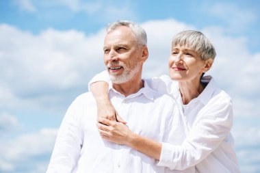 Happy senior couple in white shirts embracing under blue sky stock vector