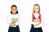 two cute multicultural schoolgirls holding books and smiling at camera isolated on white