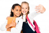 happy schoolgirl taking selfie while hugging african american friend isolated on white