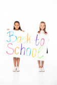 two cheerful multicultural schoolgirls holding placard with back to school inscription on white background