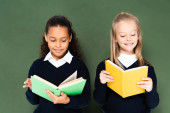 two smiling multicultural schoolgirls reading books while standing near green chalkboard