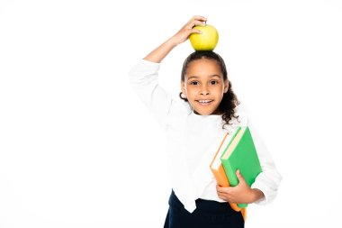 Adorable african american schoolgirl holding apple on head while standing with books isolated on white stock vector