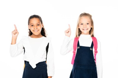 Two cheerful multicultural schoolgirls showing idea gestures while smiling at camera isolated on white stock vector