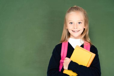 cheerful schoolgirl holding book and smiling at camera while standing near green chalkboard