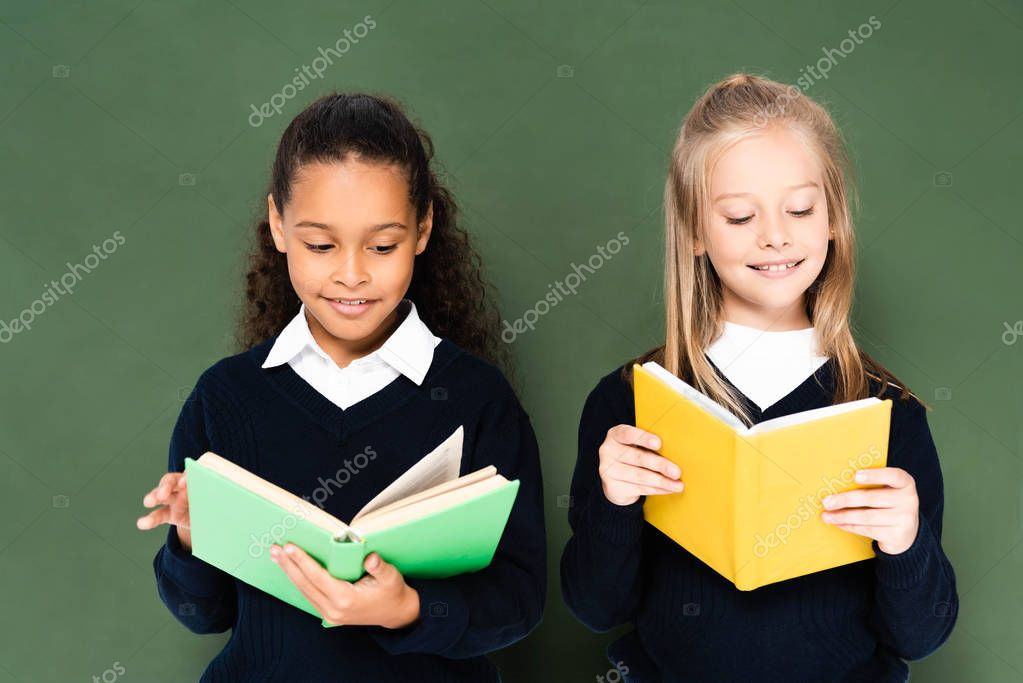 Two smiling multicultural schoolgirls reading books while standing near green chalkboard stock vector