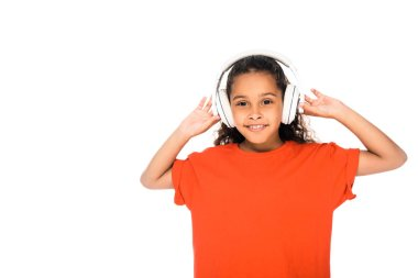 cheerful african american child listening music in headphones isolated on white